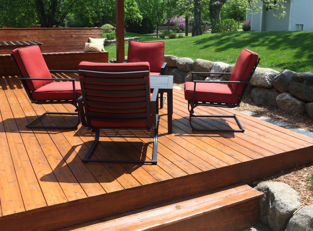 Backyard deck design with furniture on freshly stained deck.